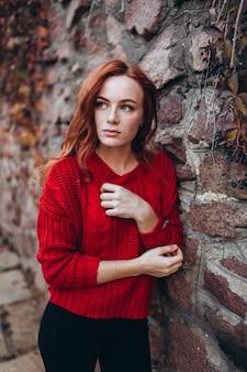Piękna imbirowa kobieta z piegami na zewnątrz w parku jesień