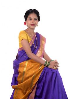 Piękna indiańska młoda dziewczyna pozuje w tradycyjnym indiańskim saree na biel przestrzeni.