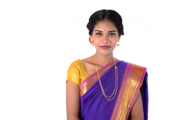 Piękna indiańska młoda dziewczyna pozuje w tradycyjnym indiańskim saree na biel ścianie