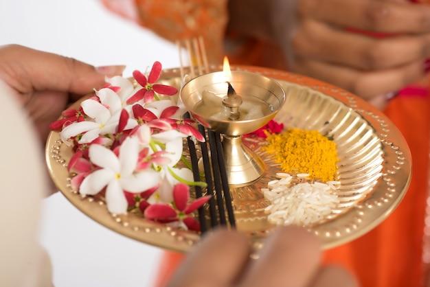 Piękna indiańska młoda dziewczyna trzyma pooja thali lub wykonuje cześć na białej ścianie