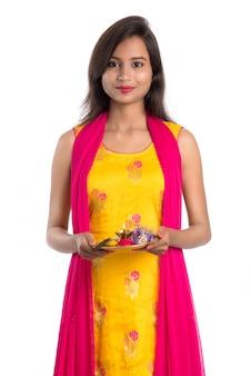 Piękna indiańska młoda dziewczyna trzyma pooja thali lub wykonuje cześć na białym tle
