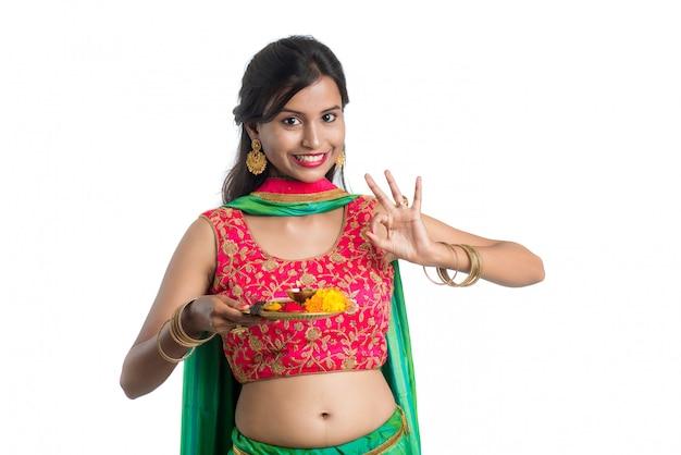 Piękna indiańska młoda kobieta trzyma pooja thali lub wykonuje cześć na białej ścianie