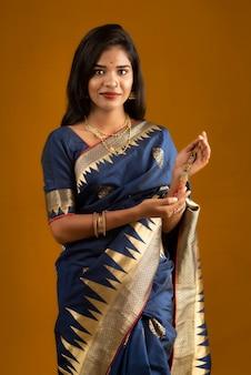Piękna indyjska dziewczyna pokazująca rakhis z okazji raksha bandhan. siostra wiąże rakhi jako symbol intensywnej miłości do brata.