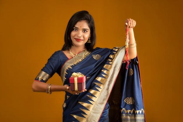 Piękna indyjska dziewczyna pokazująca rakhisa i pudełko z okazji raksha bandhan. siostra wiąże rakhi jako symbol intensywnej miłości do brata.