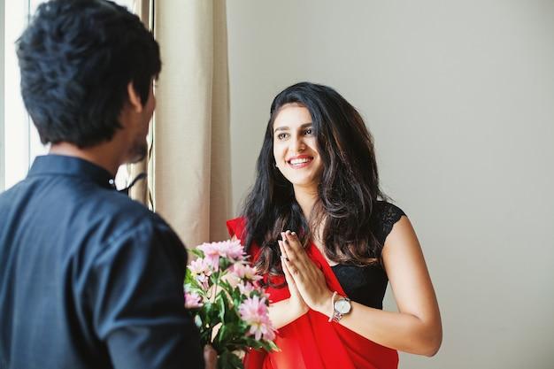 Piękna indyjska kobieta otrzymująca kwiaty z namaste