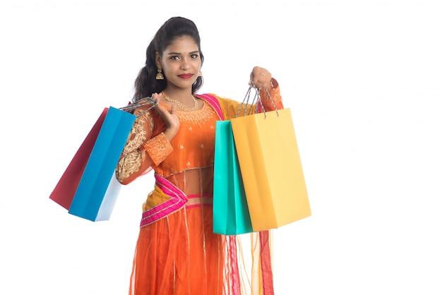 Piękna indyjska młoda dziewczyna gospodarstwa torby na zakupy podczas noszenia tradycyjnej odzieży etnicznej. pojedynczo na białej ścianie