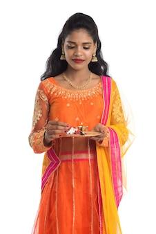 Piękna indyjska młoda dziewczyna trzyma pooja thali lub oddaje cześć