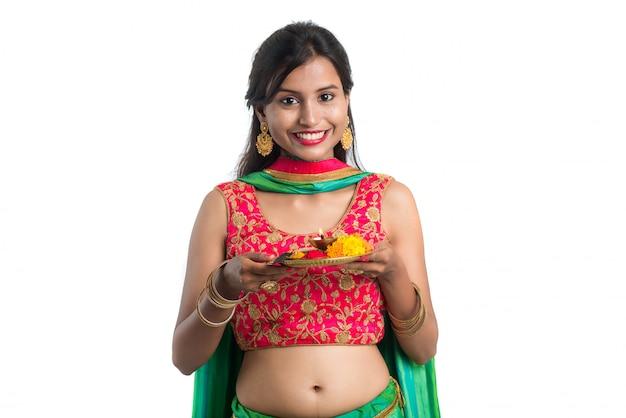 Piękna indyjska młoda dziewczyna trzyma pooja thali lub wykonuje cześć na bielu