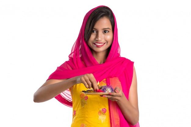 Piękna indyjska młoda dziewczyna trzyma pooja thali lub wykonuje uwielbienie na białej przestrzeni