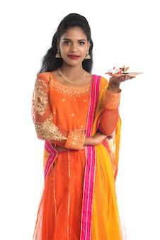 Piękna indyjska młoda dziewczyna trzyma pooja thali lub wykonywania kultu na białym tle
