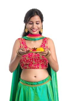 Piękna indyjska młoda dziewczyna trzyma pooja thali lub wykonywania kultu na białym