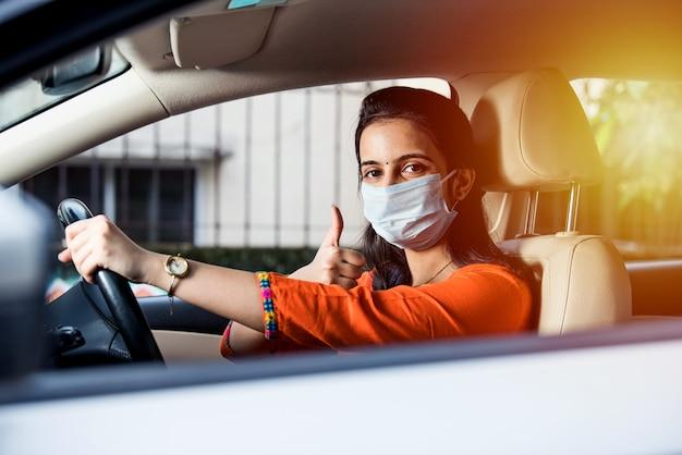 Piękna indyjska młoda dziewczyna w masce siedzi w samochodzie, maska ochronna przed koronawirusem, kierowca na ulicy miasta podczas pandemii covid-19