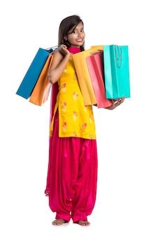 Piękna indyjska młoda kobieta trzyma i pozuje z torby na zakupy