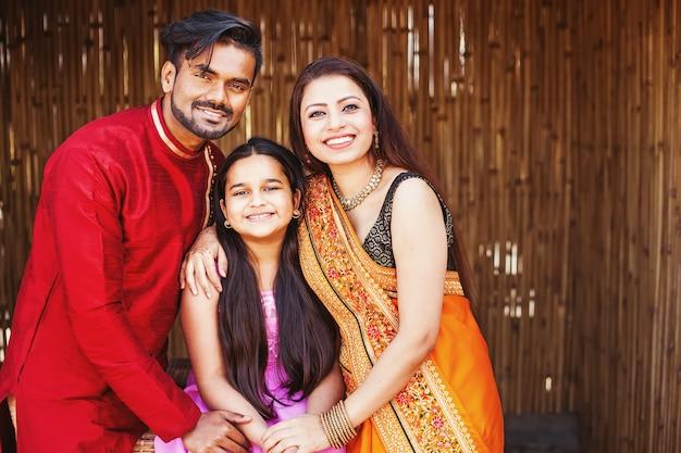 Piękna indyjska młoda rodzina uśmiecha się i patrzy na kamerę