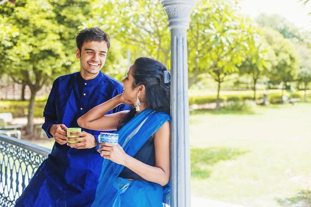 Piękna indyjska para w tradycyjnych strojach pijąca kawę na balkonie