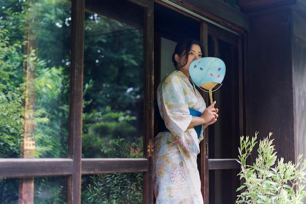 Piękna japonka ubrana w tradycyjne kimono i trzymająca w dłoni wachlarz