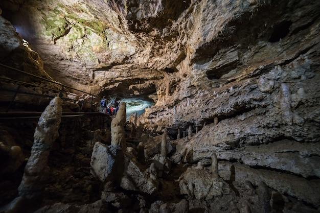 Piękna jaskinia. widok z ciemnego lochu. teksturowane ściany jaskini. obraz tła podziemia. wilgotność w jaskini. światło na końcu tunelu.
