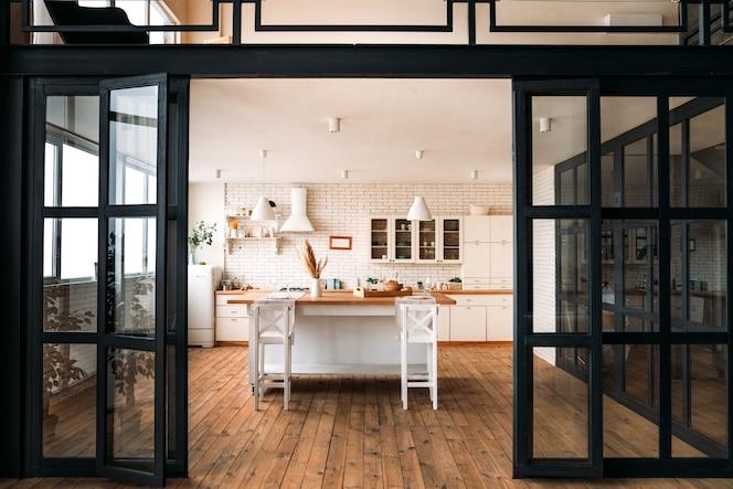 Piękna jasna kuchnia z dużym stołem i stołkami barowymi oraz białymi meblami z szerokimi szklanymi czarnymi drzwiami.