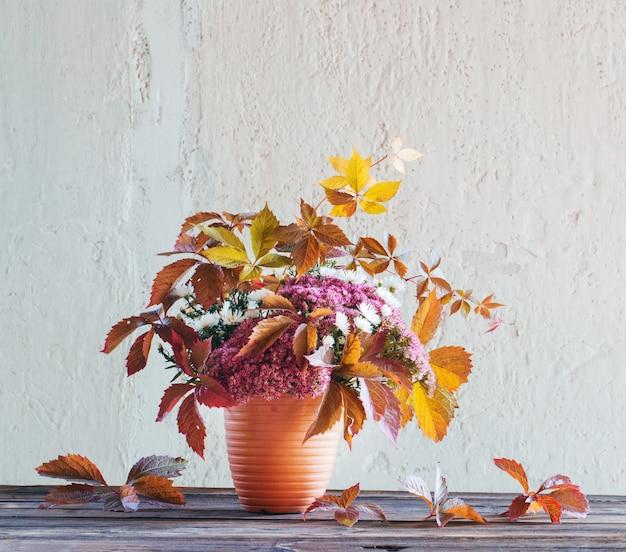 Piękna jesienna kompozycja na drewnianym stole na tle białej ściany