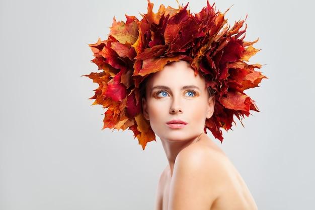 Piękna jesienna modelka kobieta z jesiennymi liśćmi klonu na głowie