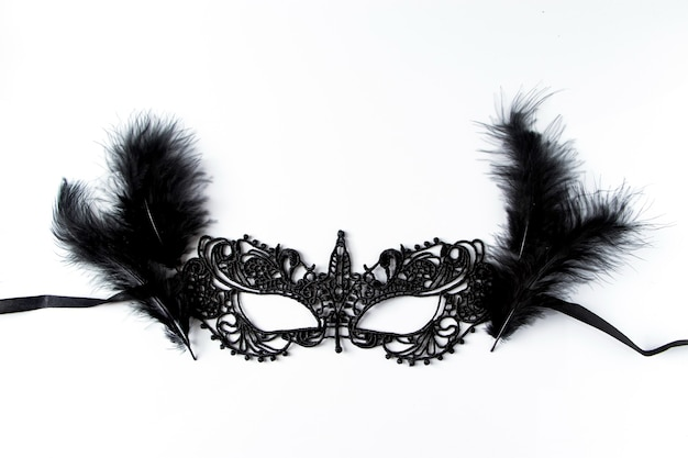 Piękna karnawałowa maska z czarnej koronki na białym tle. czarna koronkowa maska karnawałowa z piórami na białym tle.