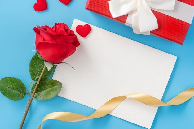 Piękna karta okolicznościowa z zaproszeniem, koncepcja dnia matki, walentynki, rocznica i urodziny na białym tle na niebieskim tle, miejsce na kopię, widok z góry, płaskie lay
