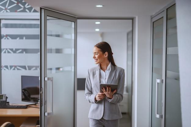 Piękna kaukaska brunetka w formalnej odzieży odprowadzeniu w biurze z pastylką w rękach. jeśli chcesz czegoś, czego nigdy nie miałeś, musisz zrobić coś, czego nigdy nie zrobiłeś.