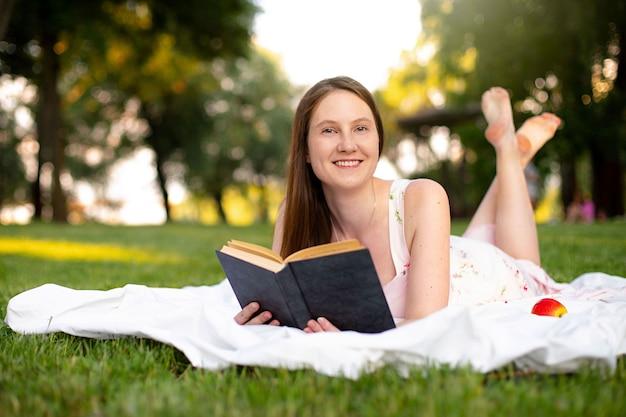 Piękna kaukaska dziewczyna czyta książkę leżąc na zielonej trawie z matą w parku