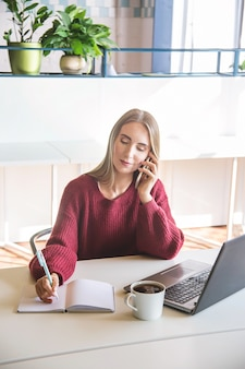 Piękna kaukaska dziewczyna mówi przez telefon i pisze w zeszycie w swoim miejscu pracy.