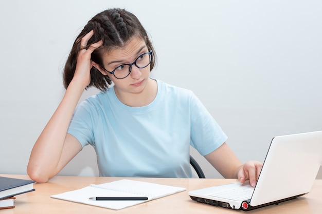 Piękna kaukaska dziewczyna siedzi przy biurku z akcesoriami szkolnymi i wygląda na zaskoczonego laptopa