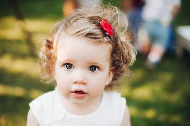 Piękna kaukaska dziewczynka z krótkimi falującymi jasnymi włosami w białej sukni w ogrodzie