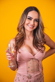 Piękna kaukaska kobieta na żółtym tle trzyma kieliszek szampana, świętuje.
