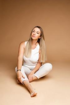 Piękna kaukaska kobieta o jasnych włosach siedzi na podłodze, obraz na białym tle na brązowym tle