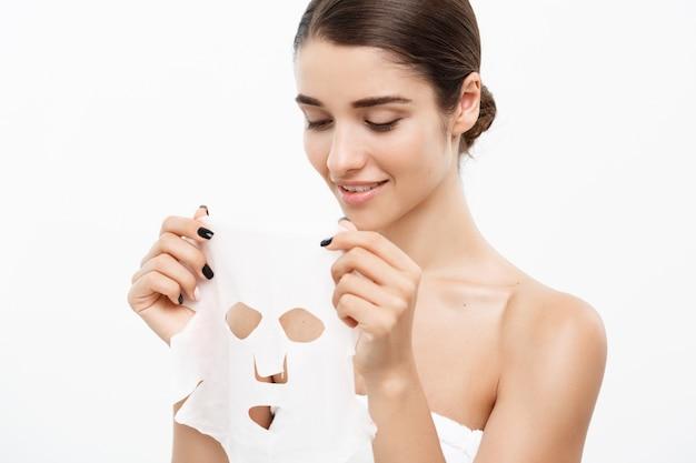 Piękna kaukaska kobieta stosuje papieru prześcieradła maskę na jej twarzy bielu tle.