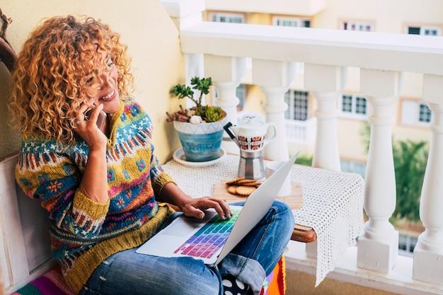 Piękna kaukaska kobieta uśmiecha się podczas pracy w domu na tarasie z laptopem i telefonem komórkowym