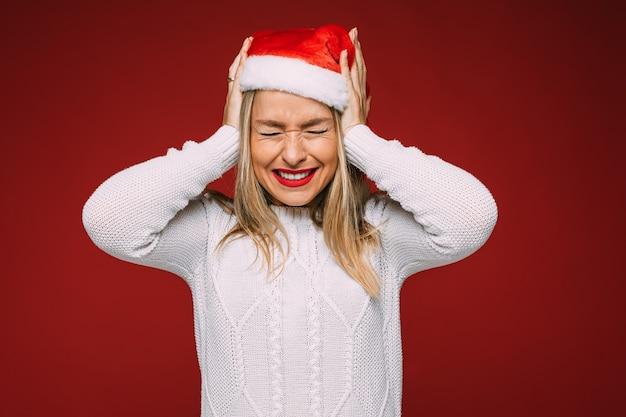 Piękna kaukaska kobieta w białym swetrze i świątecznej czapce nie chce czegoś słyszeć