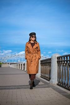Piękna kaukaska kobieta w okularach przeciwsłonecznych w czarnej czapce i kurtce pozowanie stojąc na nabrzeżu w słoneczny dzień na tle błękitnego nieba i pejzażu miejskiego