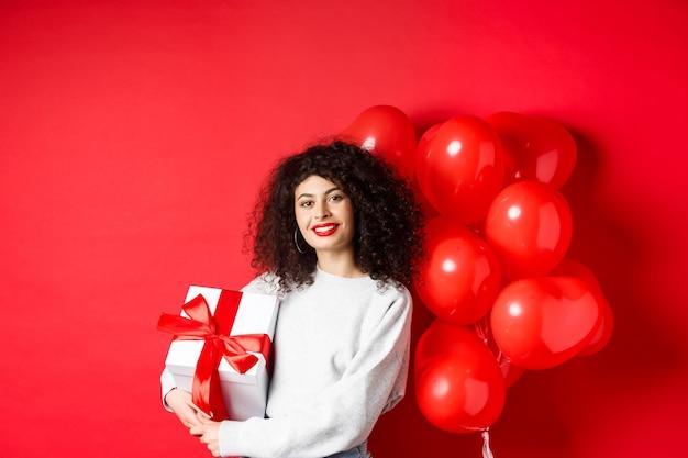 Piękna kaukaska kobieta z ciemnymi kręconymi włosami i czerwonymi ustami, stojąca z balonami w romantyczne serca i obecna w pudełku, otrzymuje prezent od kochanka, stojącego na tle studia.