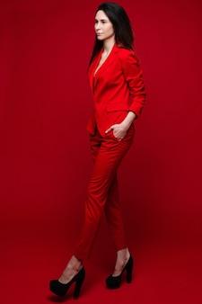 Piękna kaukaska kobieta z długimi ciemnymi prostymi włosami w czerwonym biurowym garniturze, czarnych butach