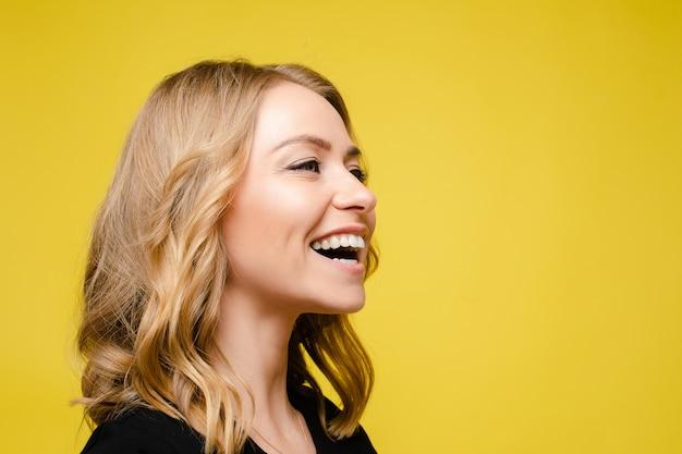 Piękna kaukaska kobieta z jasnymi falującymi włosami w czarnej koszulce śmieje się na żółtym tle