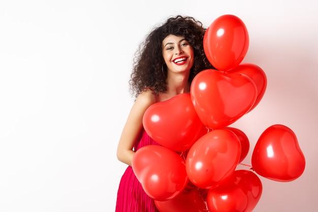 Piękna kaukaska kobieta z kręconymi włosami, noszenie sukienki randkowej, trzymając balony romantyczne czerwone serca i śmiejąc się w walentynki, stojąc szczęśliwy na białym tle.