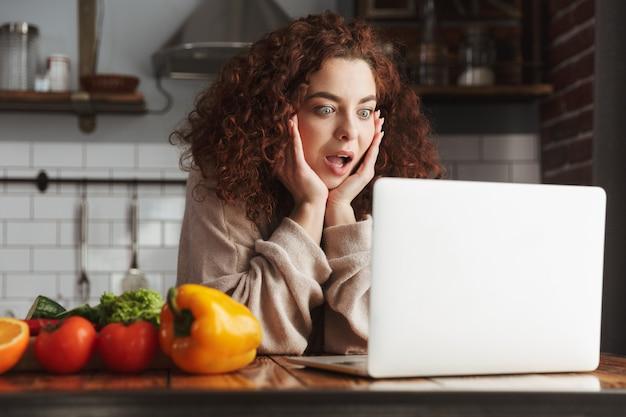 Piękna kaukaska kobieta za pomocą laptopa podczas gotowania sałatki ze świeżych warzyw we wnętrzu kuchni w domu
