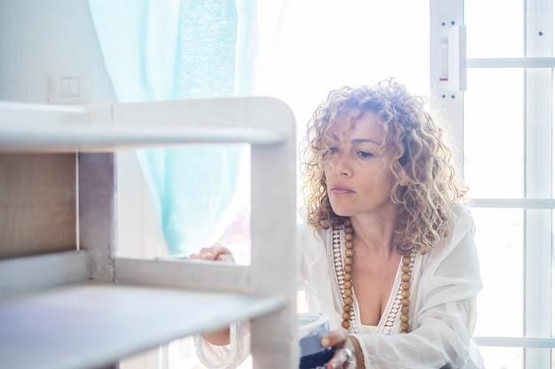 Piękna kaukaska kobieta zrób to sama meble odnowione w domu przy świetle okna. skoncentrowany wyraz dla kobiet w średnim wieku malujących białą farbą