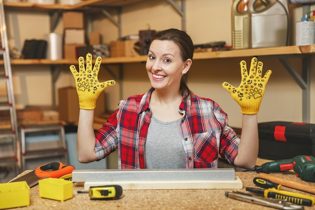 Piękna kaukaska młoda kobieta o brązowych włosach w koszuli w kratę, szara koszulka, żółte rękawiczki rozkładające ręce, pracująca w warsztacie stolarskim przy drewnianym stole z kawałkiem żelaza i drewna, różne narzędzia