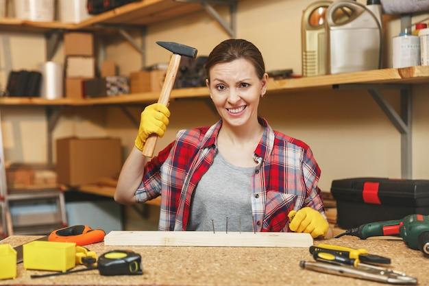 Piękna kaukaska młoda kobieta o brązowych włosach w koszuli w kratę, szary t-shirt, żółte rękawiczki, praca w warsztacie stolarskim na drewnianym stole z kawałkiem żelaza i drewna, różne narzędzia. wbijanie gwoździa.