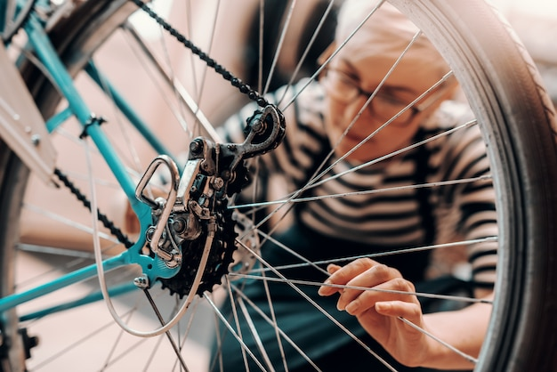 Piękna kaukaska pracownica z krótkimi blond włosami i okularami kucając i naprawiając rower. wnętrze warsztatu rowerowego.