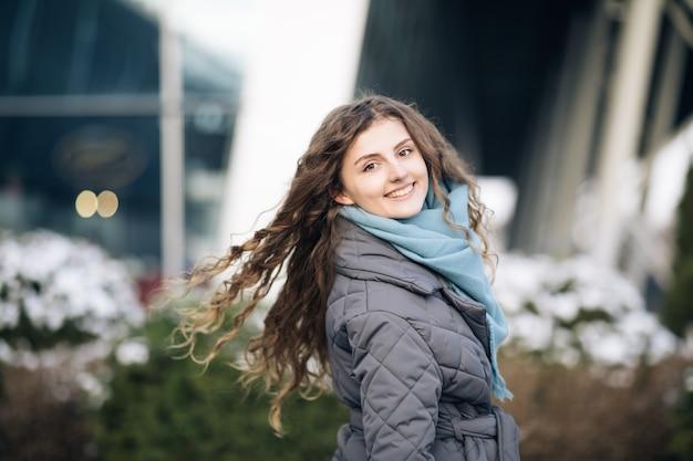 Piękna kaukaski elegancka dziewczyna z pięknymi kręconymi brązowymi włosami spaceruje szczęśliwy w centrum miasta.