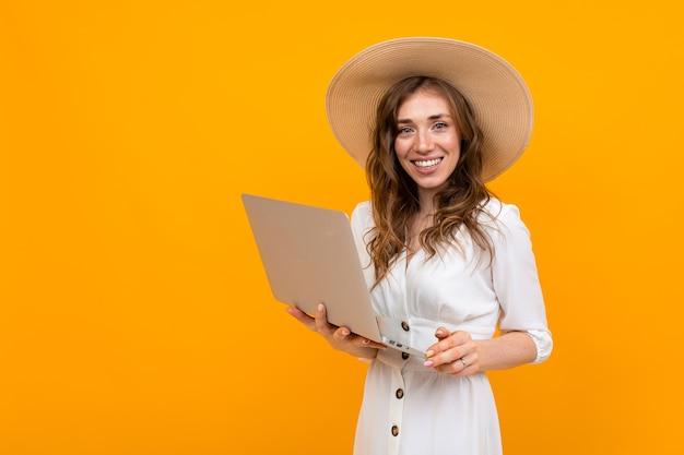 Piękna kaukaski kobieta w białym kapeluszu, okularach przeciwsłonecznych, w kostiumie działa z laptopem na białym tle na żółtym tle