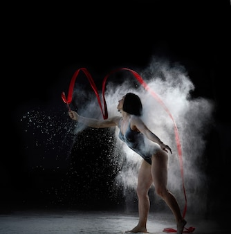 Piękna kaukaski kobieta w body z tańczącą sylwetką sportową z czerwoną wstążką