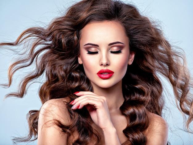 Piękna kaukaski kobieta z długimi brązowymi włosami kręconymi. portret całkiem młoda dziewczyna dorosłych. seksowna twarz atrakcyjnej pani stwarzających w studio na szarym tle.